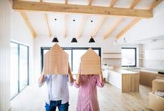 Młody pary nakrycie stawia czoło z drewnianym domem Chodzenie w nowym domu zdjęcie stock