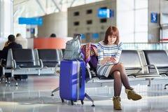 Młody pasażer przy lotniskiem, używać jej telefon obraz royalty free