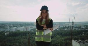 Młody piękny żeński architekt z zbawczego hełma stojakiem na wierzchołku budowa i ono uśmiecha się przy kamerą zbiory wideo