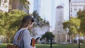 Młody piękny żeński odprowadzenie przez parka przy pracą Bizneswoman trzyma dokumenty i używa smartphone zdjęcie wideo