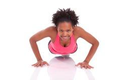 Młody piękny afrykański sprawności fizycznej kobiety robić pcha up ćwiczenia dalej obraz stock