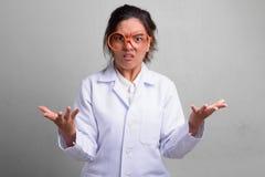 Młody piękny Azjatycki kobiety lekarki postępować szalony podczas gdy będący ubranym odkrywczość szkła zdjęcia royalty free
