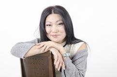 Młody piękny azjatykci kobiety obsiadanie na krześle na lekkim tle Zdjęcia Royalty Free