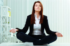 Młody piękny bizneswoman medytuje na stole Obrazy Stock