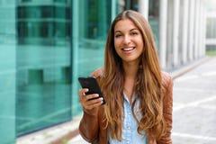 Młody piękny bizneswoman uśmiechnięty i patrzeje kamerę podczas gdy trzymający telefon komórkowego w jej ręce poj?cia prowadzenia obrazy stock