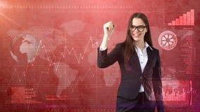Młody piękny bizneswoman z pióra writing na niewidzialnym ekranie Biznesowy i inwestorski tło z copyspace zdjęcie stock