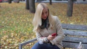 Młody piękny blond dziewczyny obsiadanie na ławce w jesień parku z telefonem w rękach zbiory