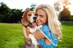 Młody piękny blondynki dziewczyny odprowadzenie, bawić się z beagle psem w parku Fotografia Royalty Free