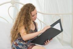 Młody piękny caucasian kobiety położenie na łóżku i sprawdzać dokumencie Fotografia Royalty Free