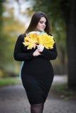 Młody piękny caucasian plus rozmiaru model w czerni sukni outdoors, xxl kobieta na naturze, jesieni atmosfera Obrazy Stock
