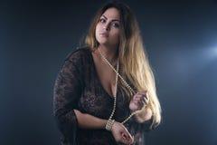 Młody piękny caucasian plus rozmiaru model, xxl kobieta w czarnym peignoir na dymiącym tle zdjęcia stock
