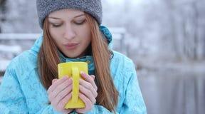 Młody piękny dziewczyny dmuchanie na gorącej herbaty lub kawy pozyci na brzeg zimy jezioro obraz royalty free