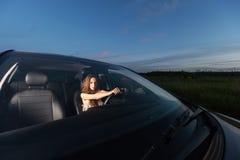 Młody piękny dziewczyny obsiadanie przy kołem samochód podróżować Outdoors i iść obraz royalty free