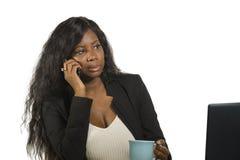 Młody piękny i ruchliwie czarny afro Amerykański bizneswoman opowiada na telefonie komórkowym przy biurowym działaniem z laptopu  fotografia royalty free