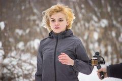 Młody piękny kobieta bieg w zimy drewnie przy kamerą zdjęcia stock