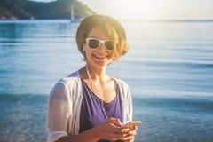 Młody piękny kobieta modnisia podróżnik w hełmofonach z mo i Fotografia Stock