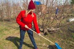 Młody piękny kobieta rolnik czyści świntuch suchej trawy, jest ubranym czerwoną kurtkę, buty i kapelusz, fotografia stock