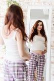 Młody piękny kobieta w ciąży stoi blisko lustra w domu zdjęcia stock