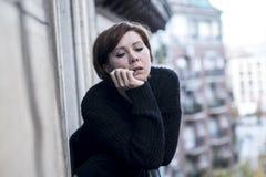 Młody piękny kobiety główkowanie i uczucia cierpienia smutna depresja przy miastowym miasta tłem stwarzamy ognisko domowe balkon obraz stock