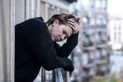 Młody piękny kobiety główkowanie i uczucia cierpienia smutna depresja przy miastowym miasta tłem stwarzamy ognisko domowe balkon obrazy stock