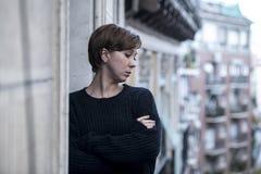 Młody piękny kobiety główkowanie i uczucia cierpienia smutna depresja przy miastowym miasta tłem stwarzamy ognisko domowe balkon fotografia royalty free