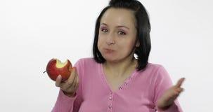 Młody piękny kobiety jeść duży, świeży i soczysty czerwony jabłko na białym tle, zbiory