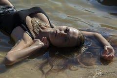 Młody piękny kobiety lying on the beach w wodzie Obrazy Stock