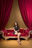 Młody piękny kobiety obsiadanie na czerwonej aksamitnej kanapie w interi Zdjęcie Stock