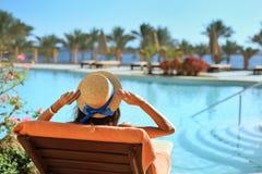 Młody piękny kobiety obsiadanie Na słońc Loungers basenem przy hotelem w kapeluszu obraz royalty free