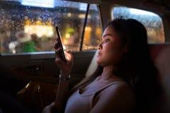 Młody piękny kobiety obsiadanie w taxi samochodzie podczas gdy używać telefon komórkowego przy nocą obraz stock