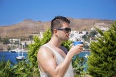 Młody piękny mężczyzna pije koktajl w tropikalnym ogródzie Obraz Stock