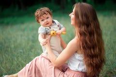 Młody piękny macierzysty obsiadanie z jej małym synem przeciw zielonej trawie Szczęśliwa kobieta z jej chłopiec na lecie pogodnym Obrazy Stock