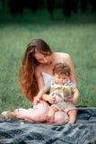 Młody piękny macierzysty obsiadanie z jej małym synem przeciw zielonej trawie Szczęśliwa kobieta z jej chłopiec na lecie pogodnym Obrazy Royalty Free