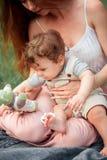 Młody piękny macierzysty obsiadanie z jej małym synem przeciw zielonej trawie Szczęśliwa kobieta z jej chłopiec na lecie pogodnym Fotografia Royalty Free