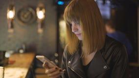 Młody piękny miedzianowłosy kobiety obsiadanie w kawiarni, barze lub używać smartphone zbiory wideo