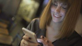 Młody piękny miedzianowłosy kobiety obsiadanie w kawiarni, barze lub używać smartphone zdjęcie wideo