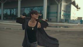 Młody piękny modniś kobiety odprowadzenie na ulicie i nieść dalej ręki jeździć na deskorolce lub longboard zbiory wideo