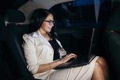 Młody piękny pomyślny bizneswomanu obsiadanie w luksusowym używać laptopie i samochodzie zdjęcie royalty free