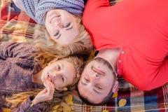 Młody piękny rodzinny lying on the beach na ono uśmiecha się i szkockiej kracie zdjęcie royalty free
