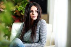 Młody piękny rozważny kobiety obsiadanie na kanapie w domu zdjęcia royalty free