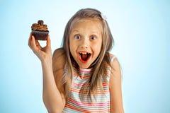 Młody piękny szalony szczęśliwy, z podnieceniem blond dziewczyny lat trzyma pączek na jej ręce patrzeje i lub zdjęcie stock
