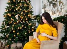 Młody piękny szczęśliwy kobieta w ciąży w długim kolor żółty sukni siti Obraz Royalty Free