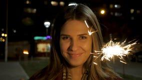 Młody piękny szczęśliwy uśmiechnięty dziewczyny mienia sparkler na ulicie Wakacyjny pojęcie Dziewczyna z sparklers w ulicie Zdjęcie Stock