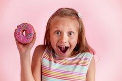 Młody piękny szczęśliwy, z podnieceniem blond dziewczyny lat trzyma pączek na jej ręce patrzeje i lub obrazy stock
