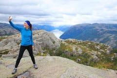 Młody piękny wycieczkowicz ono bierze selfie na jej sposobie szczyt ambony skała Preikestolen, zarząd miasta Forsand zdjęcie stock