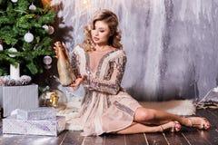 Młody piękny zadumany kobiety obsiadanie na podłogowej pobliskiej choince z zamkniętymi oczami Ładna dziewczyna w wieczór sukni p zdjęcie stock