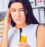 Młody piękny zmęczony chory kobiety obsiadanie w miejscu pracy w biurowej mienie butelce z pigułkami Żeński czuciowy bad przy pra zdjęcia royalty free