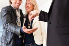 Młody pośrednik handlu nieruchomościami jest z kluczami w mieszkaniu Obrazy Royalty Free