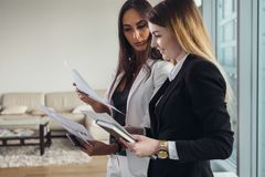 Młody pośrednik w handlu nieruchomościami pokazuje mieszkanie i dyskutuje z klientem kontrakt i innych dokumenty Fotografia Royalty Free