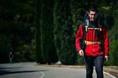 Młody podróżnik iść na opustoszałej drodze w górach Zdjęcia Royalty Free